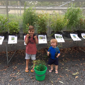 two young boys holding native plants from the community nursery