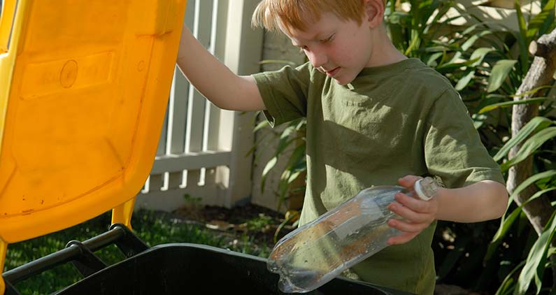 boy putting bottle in recycling bin