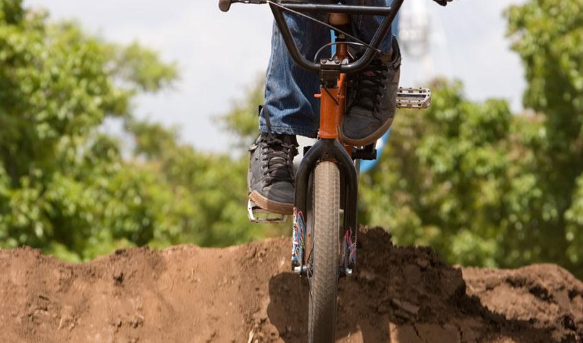 BMX rider jumping over dirt