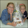 Photo of two young girls with their completed gingerbread house.